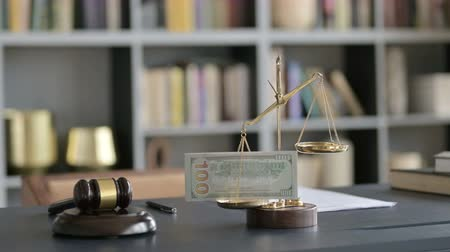 libra : Close up Shoot of Scale holding Money with Gravel on Court Desk Stock Footage