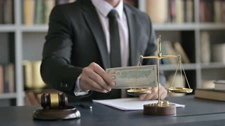 libra : Close up Shoot of Lawyer Hand putting Money in Scale