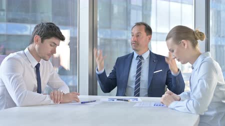 emocional : Middle Aged Businessman having getting Angry at Assistants on Office Table