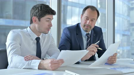 banking document : Ambitious Businessmen Discussing Project on Documents Stock Footage