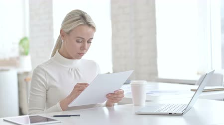 introspection : Successful Young Businesswoman Reading Documents in Office Stock Footage