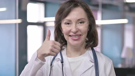 medical student : Portrait of Successful Middle Aged Professional Doctor Looking and doing Thumbs Up
