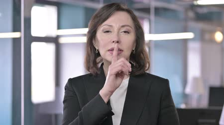 señal de silencio : Portrait of Middle Aged Businesswoman asking to be Silent by putting Finger on Lips