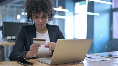 etnia africano : Serious Businesswoman Making Online Payment by Credit Card on Laptop in Office Stock Footage