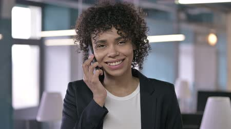 answering : Portrait of Cheerful African Businesswoman Talking on Smartphone and Smiling