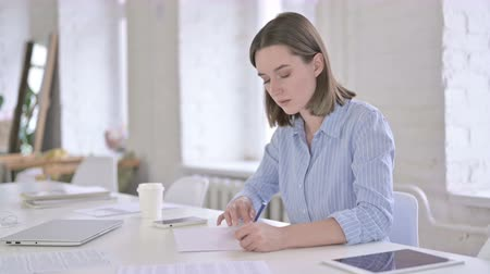 возвращение : Focused Young Woman Writing on Papers in Office