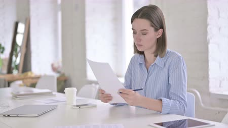 introspection : Hardworking Young Woman Reading Documents in Office