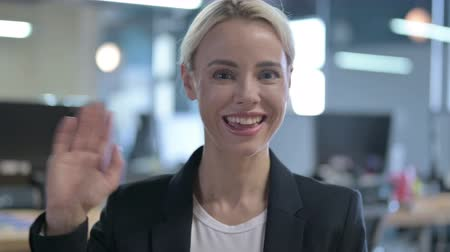 歓迎 : Portrait of Cheerful Businesswoman Waving at Camera 動画素材