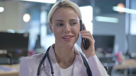 bellen : Young Doctor Talking on Phone with Patient Stockvideo