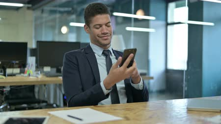 a böngésző : Young African Businessman using Smartphone in Office Stock mozgókép