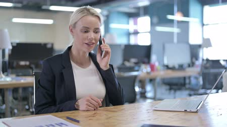negotiate : Cheerful Businesswoman Talking on Smartphone at Work