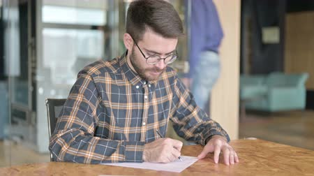 banking document : Focused Young Designer Writing on Paper in Office