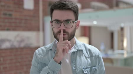 шум : Portrait of Sneaky Young Male Designer Putting Finger on Lips Стоковые видеозаписи