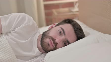 sobre o branco : Attractive Young Man Trying to Sleep in Bed