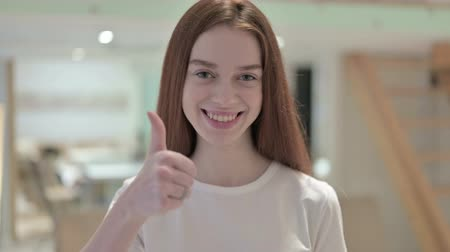 awe : Portrait of Ambitious Redhead Young Woman doing Thumbs Up