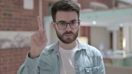 adults only : Portrait of Young Male Designer saying No with Finger Sign