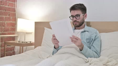 introspection : Hardworking Young Designer Reading Documents in Bed Stock Footage