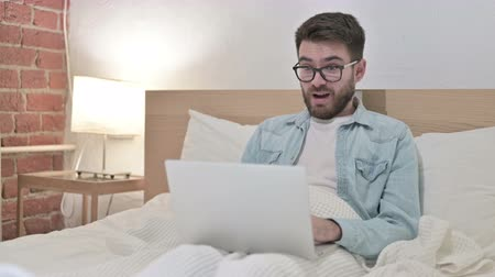 webpage : Ambitious Male Designer Celebrating Success on Laptop in Bed