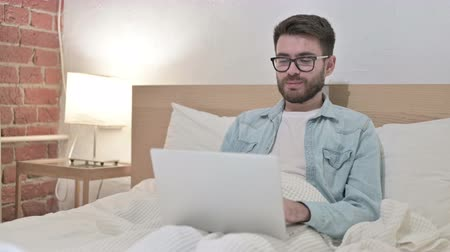 answering : Young Male Designer doing Video Chat on Laptop in Bed Stock Footage