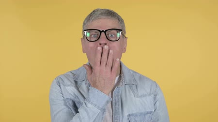 expectativa : Shocked Casual Senior Man Wondering in Awe, Yellow Background