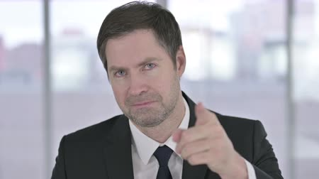 merging : Portrait of Middle Aged Businessman Pointing Finger at Camera Stock Footage