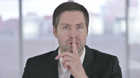 one man only : Portrait of Middle Aged Businessman Putting Finger on Lips Stock Footage