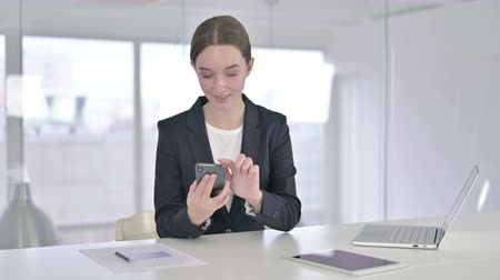 a böngésző : Focused Young Businesswoman Using Smart Phone in Office Stock mozgókép