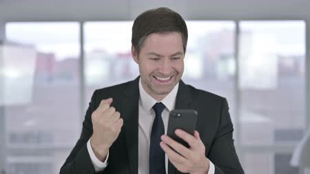 buying online : Cheerful Middle Aged Businessman Celebrating on Smartphone