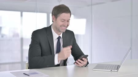 buying online : Middle Aged Businessman Celebrating Success on Smartphone