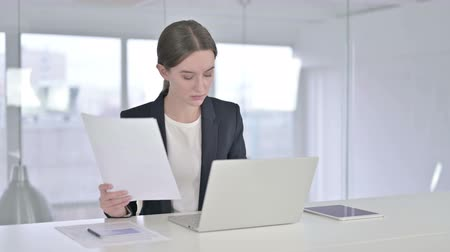 bir genç kadın sadece : Hardworking Young Businesswoman Reading Documents in Office Stok Video