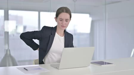 ortopedia : Tired Young Businesswoman having Back Pain in Office