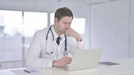introspection : Middle Aged Doctor Thinking and Working on Laptop