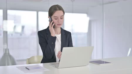 negotiations : Happy Young Businesswoman Talking on Smart Phone in Office