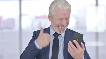 colarinho branco : Portrait of Old Senior Businessman Celebrating Success on Smartphone