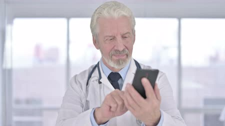 gyógyász : Portrait of Cheerful Senior Old Doctor using Smartphone in Office Stock mozgókép