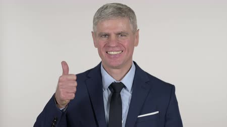 stary : Senior Businessman Gesturing Thumbs Up on White Background