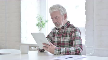 a böngésző : Hardworking Casual Old Man Using Tablet in Office Stock mozgókép