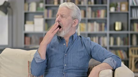 one man only : Portrait of Sleepy Senior Man Yawning on Sofa
