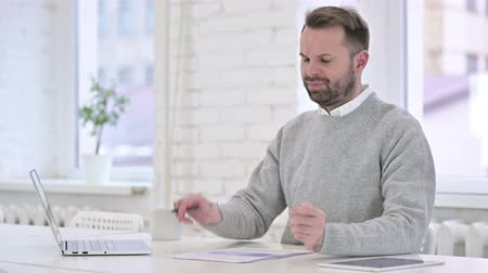 introspection : Man Upset after Reading Documents at Work