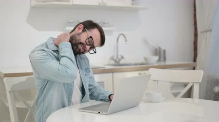 ortopedia : Tired Beard Young Man having Neck Pain in Office