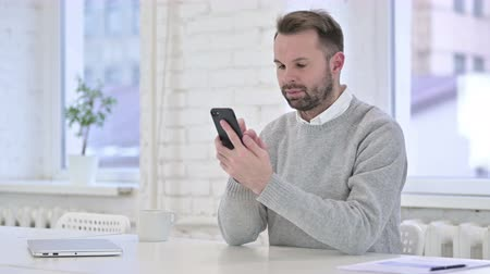 a böngésző : Successful Creative Man Using Smartphone in Office