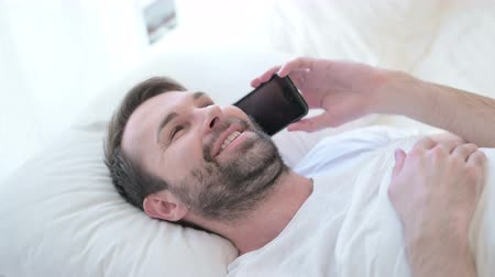cadran : Cheerful Beard Young Man Designer talking on Smartphone in Bed Vidéos Libres De Droits
