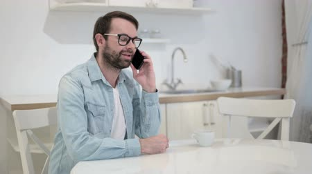 hang : Cheerful Beard Young Man Talking on Smartphone in Office