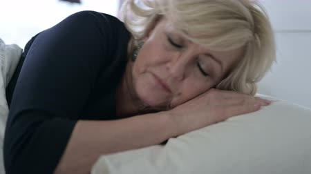 acordar : Tired Old Woman Going to Bed and Sleeping Stock Footage