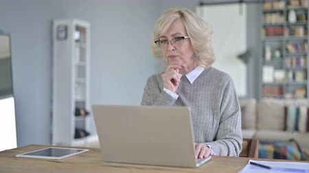 él : Old Woman Thinking and working on Laptop in Modern Office Stock mozgókép