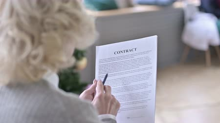 banking document : Rear View of Focused Old Woman Reading Contract