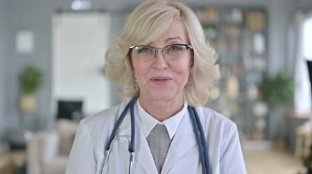negotiate : Portrait of Old Female Doctor doing Video Chat Stock Footage