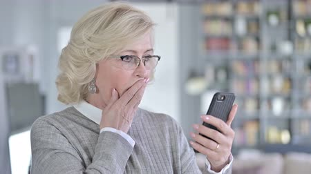 distraught : Portrait of Sad Old Woman Reacting to Loss on Smartphone