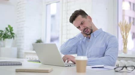 uncomfortable : Creative Man having Neck Pain at Work
