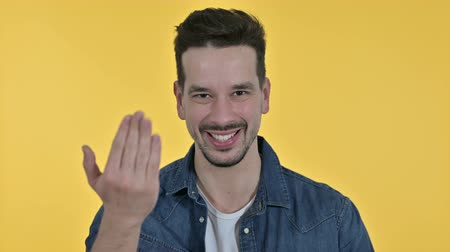 merging : Portrait of Handsome Young Man Pointing Finger and Inviting, Yellow Background